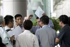 <p>Customers of MF Global swarm around an unidentified employee holding a stack of withdrawal request forms in Singapore, in the lobby of its office, November 1, 2011. REUTERS/The Straits Times/Lau Fook Kong</p>