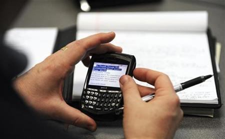 A man checks his Blackberry during in this file photo. REUTERS/Dave Kaup