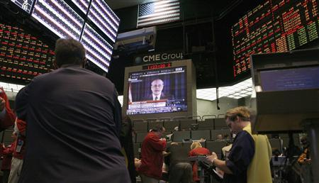 Traders in the two and five year options pit at the Chicago Board of Trade signal orders as a television screen shows Federal Reserve Chairman Ben Bernanke speaking during a news conference, in Chicago, November 2, 2011.  REUTERS/Frank Polich