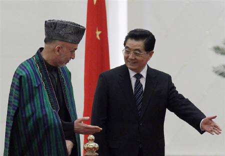 China's President Hu Jintao (R) shows the way to Afghanistan's President Hamid Karzai during a welcome ceremony inside the Great Hall of the People in Beijing, March 24, 2010. REUTERS/David Gray/Files