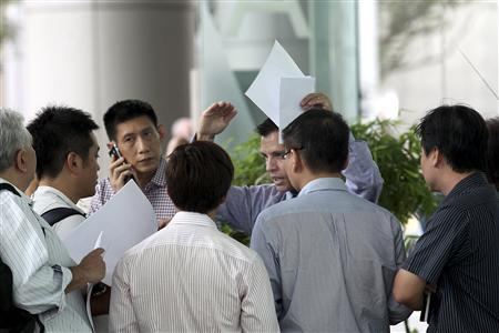 Customers of MF Global swarm around an unidentified employee holding a stack of withdrawal request forms in Singapore, in the lobby of its office, November 1, 2011. REUTERS/The Straits Times/Lau Fook Kong
