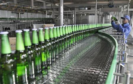 An employee checks a bottle of beer at an assembly line of a Tsingtao brewery in Rizhao, Shandong province January 20, 2011.  REUTERS/Stringer