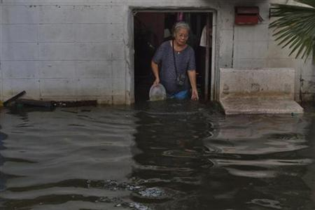 An elderly woman clears debris from the front door of her flooded residence in Bangkok November 2, 2011.  REUTERS/Adrees Latif