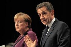 Президент Франции Николя Саркози (справа) и канцлер Германии Ангела Меркель выступают на пресс-конференции в Каннах, 2 ноября 2011 года. Лидеры Германии и Франции заявили Греции в среду, что страна не получит ни цента европейской помощи, пока не решит, хочет ли остаться в еврозоне, и дали понять, что сохранение евро, в конечном счете, для них важнее, чем спасение Греции. REUTERS/Charles Platiau