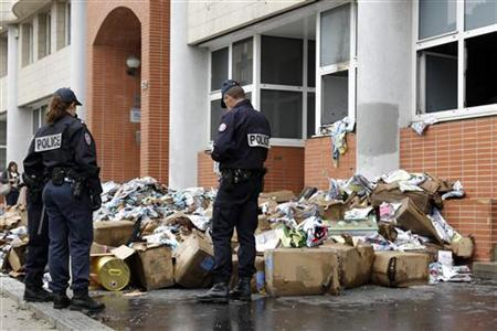 French police stand in front of the damaged offices of French satirical magazine Charlie Hebdo in Paris, November 2, 2011.REUTERS/Benoit Tessier