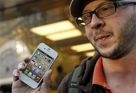 Chris Centers displays his new iPhone 4S after making the purchase at Apple's flagship retail store in San Francisco, California October 14, 2011. REUTERS/Robert Galbraith