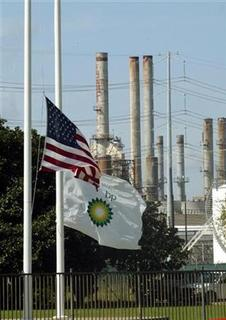 Flags fly at half staff outside the British Petroleum refinery in Texas City, Texas March 24, 2005 with the refining plant in the background the day after an explosion rocked the plant.   REUTERS/Richard Carson