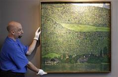 """<p>Un empleado ubica la obra """"Litzlberg on the Attersee"""", de Gustav Klimt durante una subasta de la casa de remates Sotheby's en Nueva York, oct 19 2011. Sotheby's registró una impresionante venta de arte modernista e impresionista por 200 millones de dólares, encabezada por un paisaje de Klimt colocado por 40 millones de dólares, en una subasta que batió récords y ayudó a reafirmar el inestable mercado del arte. REUTERS/Brendan McDermid</p>"""