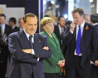 Italy's Prime Minister Silvio Berlusconi walks past Germany's Chancellor Angela Merkel and Britain's Prime Minister David Cameron before a working session at the G20 Summit of major world economies in Cannes, November 3, 2011.    REUTERS/Toby Melville