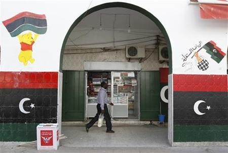 A man walks in a souk decorated with Kingdom of Libya flag in downtown Tripoli October 30, 2011.  REUTERS/Jamal Saidi