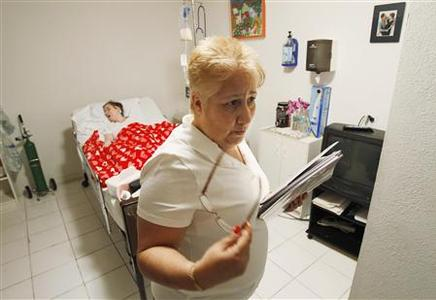 Linda Carmona-Sanchez tends to her critically-ill and bed-ridden daughter Carmen, 28, at their home in Kendall, Florida October 4, 2011.  REUTERS/Hans Deryk