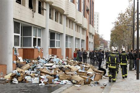 Firefighters walk in front of the damaged offices of French satirical magazine Charlie Hebdo in Paris November 2, 2011. REUTERS/Benoit Tessier