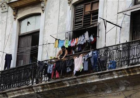 A woman hangs her laundry from the balcony of her colonial-era apartment in Havana July 3, 2011. REUTERS/Desmond Boylan