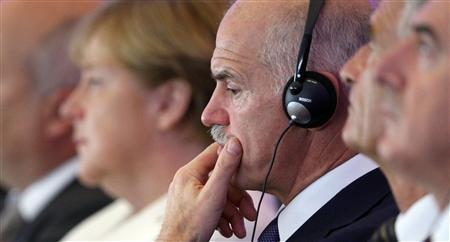 German Chancellor Angela Merkel (L) and Greek Prime Minister George Papandreou attend a meeting of the BDI (Federational German Industries) in Berlin September 27, 2011.  REUTERS/Tobias Schwarz/Files