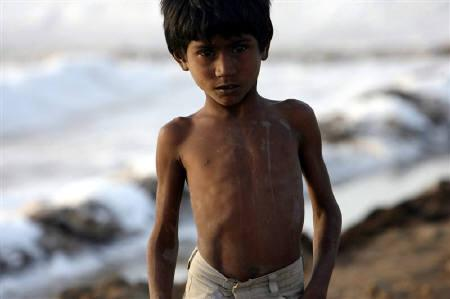 A worker's son poses for a picture at a salt pan near Bhavnagar, in Gujarat March 5, 2009. REUTERS/Arko Datta/Files