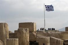Греческий флаг на руинах афинского акрополя 3 ноября 2011 года. Греция передумала созывать референдум и готова принять помощь Евросоюза, но для этого правительству надо получить вотум доверия, ради которого премьер-министр Георгиос Папандреу согласился уйти в отставку и отдать власть коалиционному правительству. REUTERS/John Kolesidis