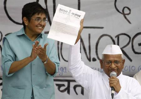 Social activist Anna Hazare displays a note from the Indian government to his supporters as former Indian police officer and social worker Kiran Bedi watches after he called off his hunger strike during a campaign against corruption in New Delhi April 9, 2011. REUTERS/Parivartan Sharma/Files