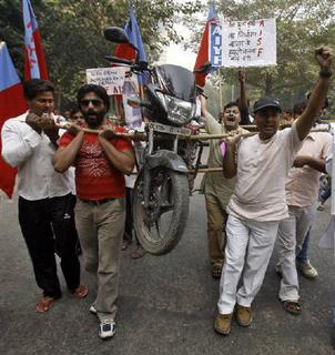 Demonstrators carry a motor bike with the help of bamboo sticks to protest a price hike in petrol in New Delhi November 4, 2011.  REUTERS/Parivartan Sharma