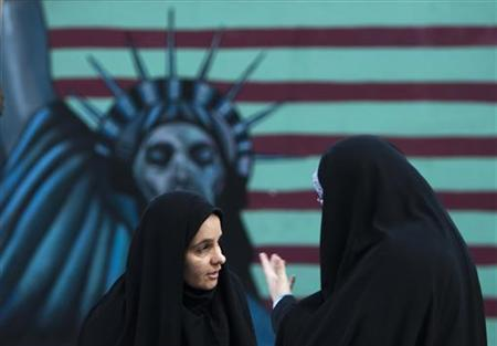 Iranian women stand in front of an anti-U.S. mural painted on the wall of the former U.S. Embassy in Tehran, November 4, 2011. REUTERS/Raheb Homavandi