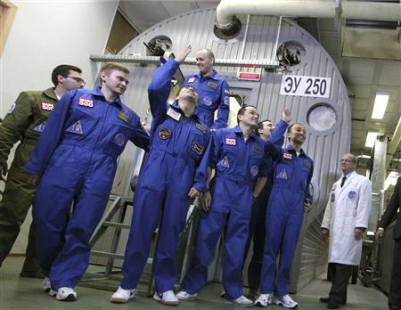 Mars500 experiment crew members react after leaving the mock spaceship in Moscow November 4, 2011.  REUTERS/IBMP/Oleg Voloshin/Handout
