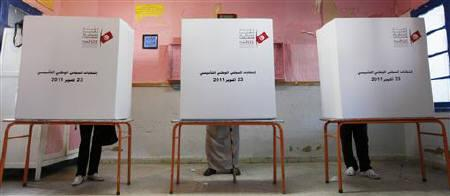 People fill up their ballot papers at a polling station during general elections in Marsa, north Tunisia October 23, 2011. REUTERS/Jamal Saidi/Files