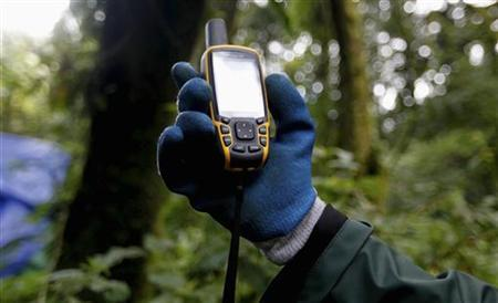 A scientist holds up a GPS device inside Bwindi Impenetrable National Park, Uganda, October 14, 2011. REUTERS/Edward Echwalu