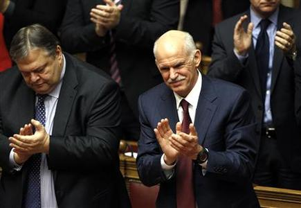 Greek Prime Minister George Papandreou (R) and Finance Minister Evangelos Venizelos applaud after winning a vote of confidence in the Greek parliament in Athens November 5, 2011. REUTERS/Yiorgos Karahalis