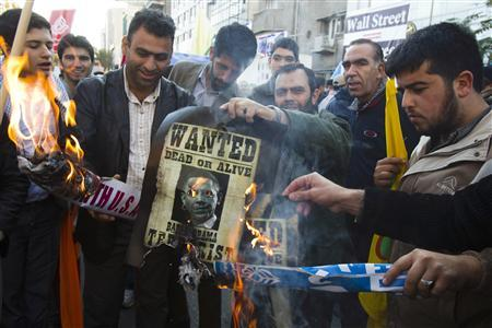 EDITORS' NOTE: Reuters and other foreign media are subject to Iranian restrictions on their ability to film or take pictures in Tehran.  Iranian men burn a picture of U.S. President Barack Obama during an anti-U.S. gathering in front of the former U.S. Embassy in Tehran November 4, 2011. REUTERS/Raheb Homavandi
