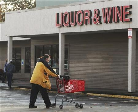 A customer walks past a Washington State liquor store in Seattle, Washington November 3, 2011. Washington state voters will decide on a ballot initiative that would privatize liquor sales and close state package stores, a controversial measure that has drawn a lot of money from brewers and spirit makers and retailers such as Costco.  REUTERS/Anthony Bolante