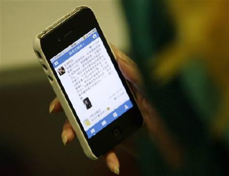 A woman loads a Chinese microblog website on her Apple iPhone in Beijing, September 16, 2011.  REUTERS/Jason Lee/Files