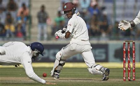 West Indies Kraigg Brathwaite plays a shot as VVS Laxman dives to stop the ball during the first day of their first test cricket match in New Delhi November 6, 2011. REUTERS/Adnan Abidi