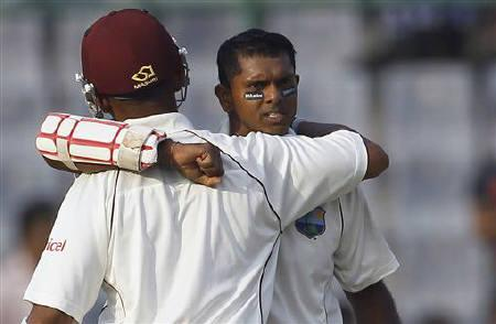 West Indies' Shivnarine Chanderpaul (R) is congratulated by his teammate Carlton Baugh after he scored a century during the first day of their first test cricket match against India in New Delhi November 6, 2011. REUTERS/Adnan Abidi