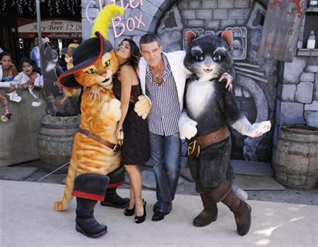 Cast members Antonio Banderas (R) and Salma Hayek (L) pose with characters at the premiere of the animated film ''Puss In Boots'' in Los Angeles October 23, 2011. REUTERS/Phil McCarten
