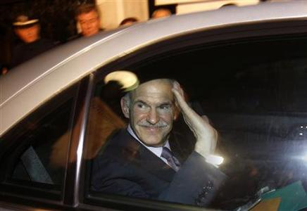 Greek Prime Minister George Papandreou waves from his car as he leaves the presidential palace after a meeting with President Karolos Papoulias and Conservative leader Antonis Samaras in Athens November 6, 2011.  REUTERS/Yannis Behrakis