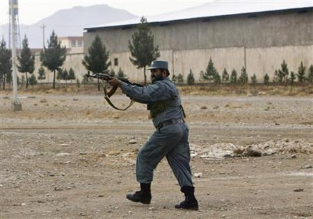 An Afghan policeman fires his rifle at insurgents following an assault by Taliban insurgents in Herat November 3, 2011.  REUTERS/Mohammad Shoib