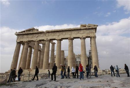 Tourists walk in front of the Parthenon temple at the archaeological site of the Acropolis hill in Athens November 3, 2011. REUTERS/John Kolesidis