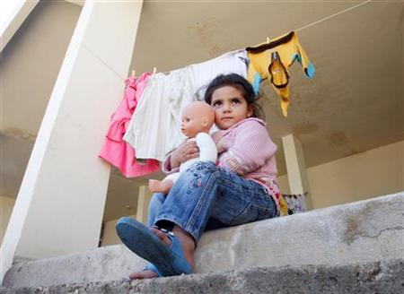 A Syrian refugee girl carries a doll that she received from a women's non-profit charity organization on the first day of Eid al-Adha, at an abandoned school in Wadi Khaled area, northern Lebanon, November 6, 2011. REUTERS/ Omar Ibrahim