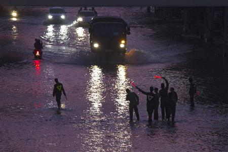 Army soldiers direct traffic at a flooded bus stop near Bangkok's Chatuchak market November 7, 2011.  REUTERS/Adrees Latif