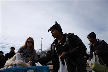 People receive items from a food bank in Gary, Indiana March 31, 2011.  REUTERS/Eric Thayer