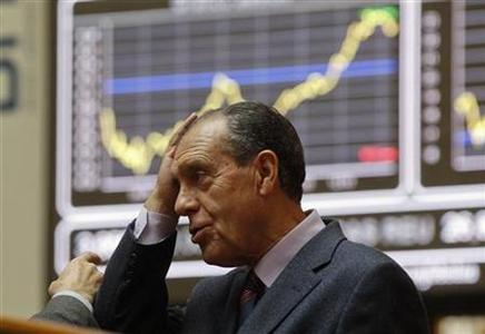 A man holds his head at the bourse in Madrid November 7, 2011. European stock futures pointed to a weaker open for equities on Monday as political uncertainties in highly-indebted Italy and Greece raised fresh concerns that the region's debt crisis would intensify and threaten a fragile global economic recovery. REUTERS/Andrea Comas (