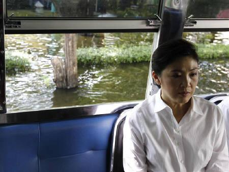 Thailand's Prime Minister Yingluck Shinawatra sits in a vehicle during her visit to a flooded area in Bangkok November 7, 2011. REUTERS/Sukree Sukplang