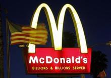 Американский флаг на фоне логотипа McDonald's в Лос-Анджелесе, 5 апреля 2011 г. Выручка крупнейшей в мире сети быстрого питания McDonald's Corp в октябре 2011 года выросла на 5,5 процента в ресторанах, открытых как минимум год назад, сообщила корпорация во вторник. REUTERS/Mario Anzuoni