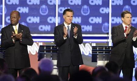 GOP presidential candidates (L-R) businessman Herman Cain, former Massachusetts Governor Mitt Romney and Texas Governor Rick Perry stand  on stage at the start of the  CNN Western Republican debate in Las Vegas, Nevada October 18, 2011.     REUTERS/Steve Marcus