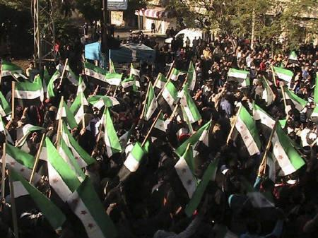 Demonstrators protesting against Syria's President Bashar al-Assad wave old Syrian flags as they march through the streets on the first day of the Muslim festival of Eid-al-Adha in Alsnmin near Daraa November 6, 2011. REUTERS/Handout