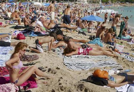 Tourists enjoy the sun on New Year's Day on Waikiki Beach in Honolulu, Hawaii January 1, 2010.         REUTERS/Larry Downing