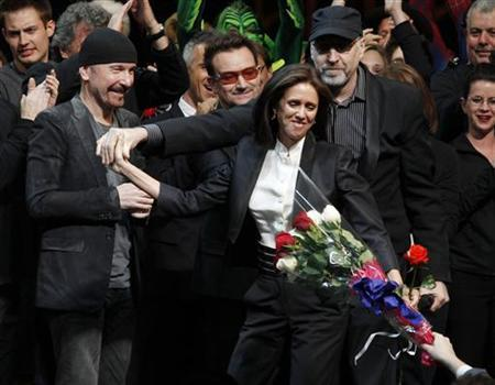 Director Julie Taymor (C) is handed a bouquet of flowers as she takes the stage along with The Edge (L) and Bono of U2 and director Philip William McKinley (R) during the curtain call for the Broadway opening of ''Spider-Man: Turn Off The Dark'' in New York City June 14, 2011. REUTERS/Jessica Rinaldi