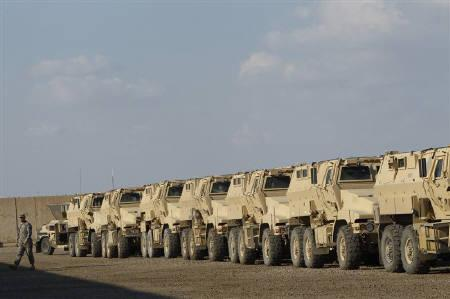 A U.S. soldier walks past parked military armoured vehicles that have ended their mission in Iraq, within Victory Base Compound in Baghdad November 7, 2011. REUTERS/Saad Shalash