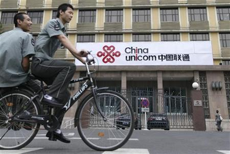 Security guards ride past a China Unicom office in Beijing September 7, 2010. REUTERS/Christina Hu
