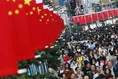 Люди проходят по улице Шанхая, украшенной национальными китайскими флагами, 30 сентября 2011 года. Инфляция в Китае, как и ожидалось, снизилась до 5,5 процента в октябре в годовом исчислении с уровня в 6,1 процента, показанного в сентябре, сообщило Национального бюро статистики КНР в среду. REUTERS/Carlos Barria