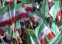 """Сторонники иранского президента Махмуди Ахмадинежада размахивают флагами, слушая его речь в провинции Бахтияри 9 ноября 2011. Ахмадинежад опроверг в среду утверждение МАГАТЭ о том, что Тегеран создает ядерное оружие - информация, заставившая Запад пригрозить Ирану """"беспрецедентными санкциями"""".REUTERS/President.ir/Handout"""